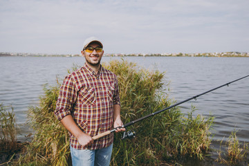 Young unshaven smiling man in checkered shirt, cap and sunglasses holds fishing pole on shore of lake on background of water, shrubs and reeds. Lifestyle, recreation, fisherman leisure concept.
