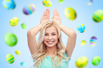 happy woman making bunny ears over easter eggs