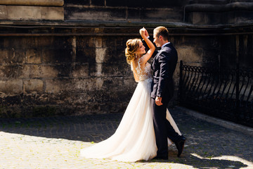 Newlyweds dance against a background of brick walls in a beautiful sunny day