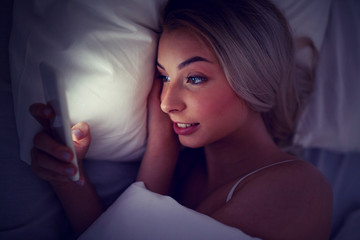 Fototapete - young woman with smartphone in bed at home bedroom