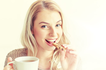 happy woman with tea eating cookie at home