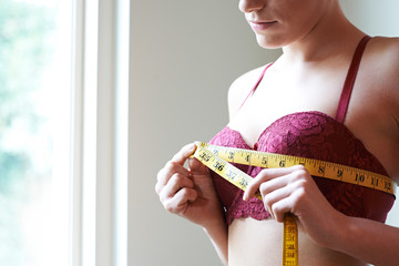 Woman Measuring Her Bra Size With Tape Measure