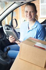 Portrait Of Female Courier In Van With Digital Tablet Delivering Package To House