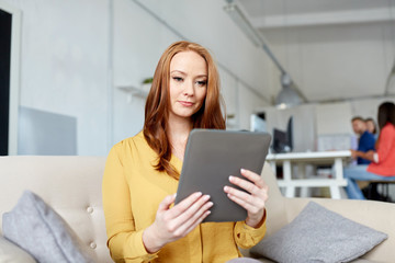 redhead woman with tablet pc working at office
