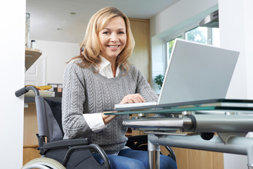 Portrait Of Disabled Woman In Wheelchair Using Laptop At Home