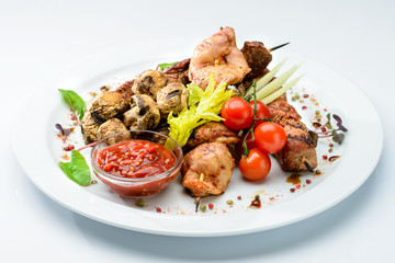 Photo sur Plexiglas Plat cuisine Appetizing dish with meat, mushrooms, tomatoes and salad at the white plate, close-up. For menu design