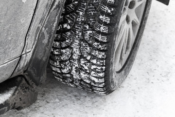 Car wheel on snow tire with metal studs