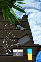 Man summer clothes collage flat lay isolated on dark wood background. Summer outfit of casual man desk top view fashion accessories: shirt, shorts, sunglasses, camera, smartphone. Holiday travel