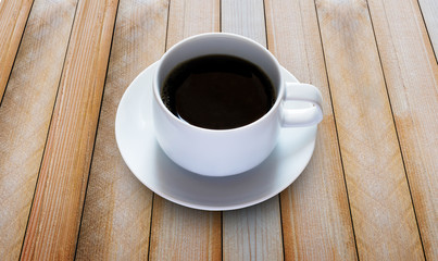 black coffee in white cup on wooden board.