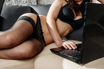 Beautiful, young girl posing in front of a web camera, working as a sexual model. The concept of online flirting, sex on the Internet.