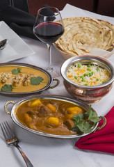 Indian curry food spread on a fancy dinner table with rice, laccha paratha, lamb aam wala, saffron malai kofta, red wine
