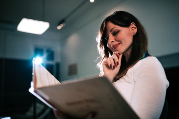 Close-up image of a beautiful female musician holding sheet music.