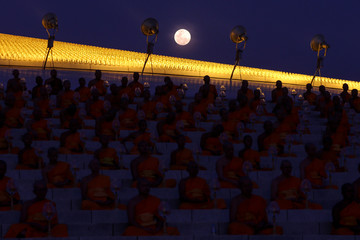 The full moon is seen as buddhist monks attend a ceremony on Makha Bucha Day at Wat Phra Dhammakaya in Pathum Thani