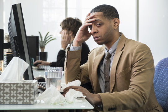 Male office worker sick at his desk
