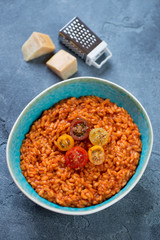 Risotto with tomatoes and parmesan cheese served in a bowl on a blue stone background, studio shot