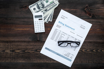 Paying bills. Billing statement near calculator, money, glasses on dark wooden background top view copy space