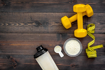 Nutrition for muscle growth. Scoop of protein near shaker, dumbbell, measuring tape on dark wooden background top view copy space