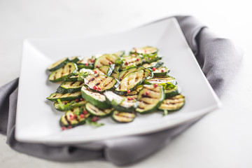 Zucchini. Grilled zucchini with red spice on white plate