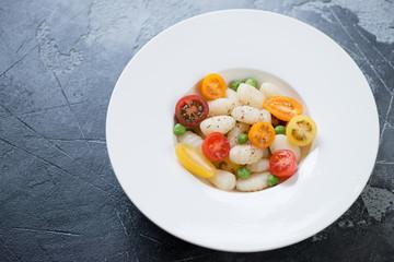 White plate with italian potato gnocchi, fresh sliced mini tomatoes and green peas on a grey concrete background, studio shot