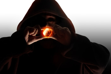 Man in hood / Hooded man in shadow holding crypto currency bitcoin on dark background.