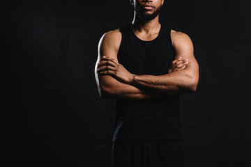 cropped shot of confident african american sportsman standing with crossed arms isolated on black