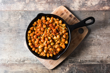 Fried spicy chickpeas in frying pan on wooden table. Top view