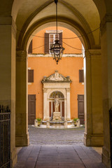 Arch with a lantern leads to courtyard with an old marble fountain, warm yellow orange colors, Rome, Italy