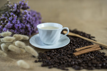 Morning coffee in white cup with decorative dried flowers, spoon , cinnamon and coffee beans background on table top, warm tone, morning time concept, selective focus