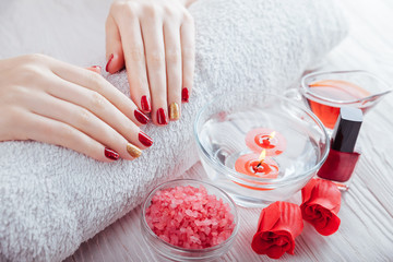 Red and golden manicure with spa essentials on white wooden table.