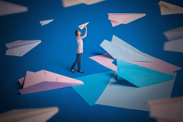 Creative surrealism design with origami paper planes. Young girl let paper airplanes. Blue, blue, pink origami crafts.