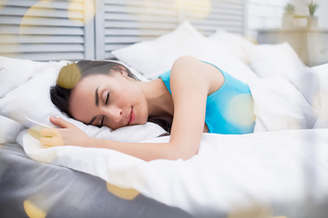 Beautiful young woman is sleeping sweetly in a white bed in her room. Rest at home.