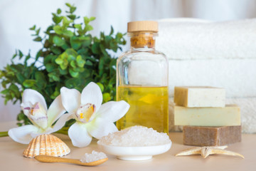 Wellness setting. Sea salt, soap, towel, oil and flowers on wooden background, spa