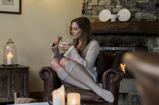 young woman in casual dressing at home relaxing by drinking hot chocolate or tea during cold autumn or winter season