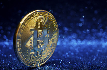 golden bitcoin coin with sparkle glitter blue background, crypto currency concept.