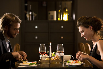 Man and woman eating during candlelight lunch.Couple in love romantic dinner at restaurant