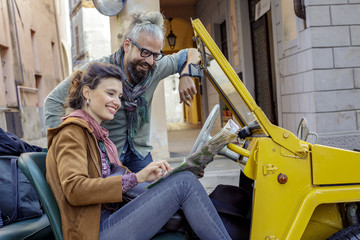 Woman and man smiling looking at map.Side view. Caucasian couple in love roadtrip vacation italian travel on convertible car