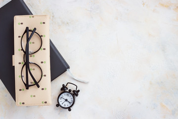 Notepad diary, business card, glasses, clock on a light table. Top view with copy space,Flat Lay