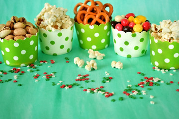 Popcorn, multicoloured drops, pretzels with salt and pistachio nuts in paper cups on green background. Snacks assortment