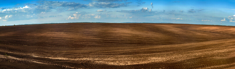 Panorama of arable land over amazing clouds sky