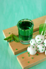 Green alcoholic drink and cake pops on green background