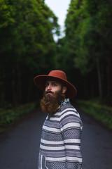 Bearded man in hat on road