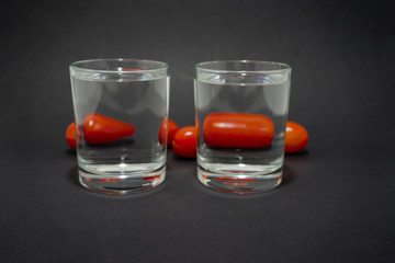cherry tomatoes through two glasses with water on a black background