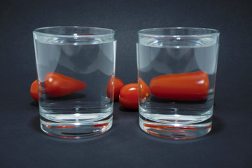 cherry tomatoes through two glasses with water on the glass