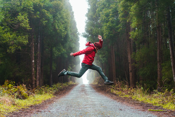 Side view of man jumping on road in forest