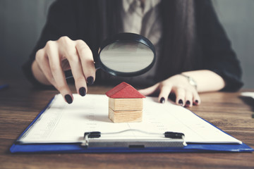 woman hand magnifier and house model