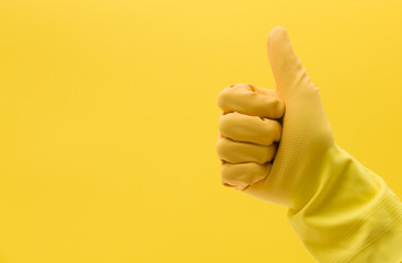 Thumbs up hand gesture made by a hand in a yellow rubber cleaning glove