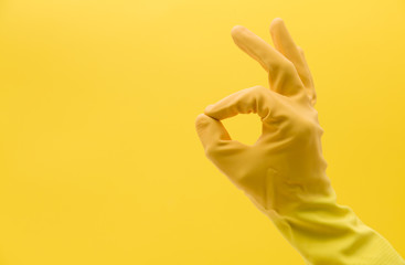Okay hand gesture made by a hand in a yellow rubber cleaning glove Wall mural