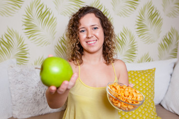 Young curly woman sitting sofa and holding a green apple and a vase of chips. Healthy eating concept.