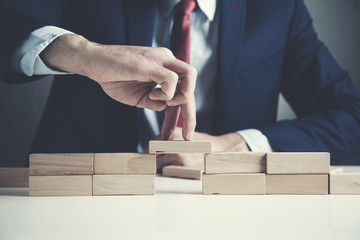 businessman hand wooden cubes on table