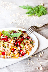 Plate of pearl barley warm salad with carrot, dill and pomegranate seeds in a plate on a wooden table, selective focus. Healthy and organic food concept. Fasting food. Vegetarian food.